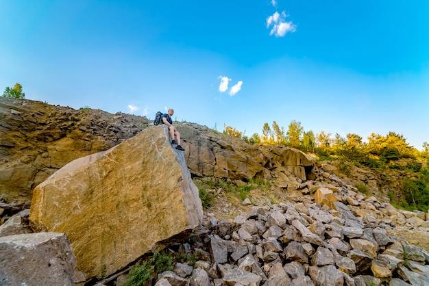 Un turista se sienta en una gran piedra en la roca en el verano.