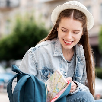 Turista sonriente en la ciudad con un sombrero
