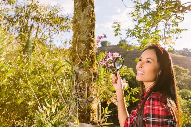 Turista sonriente que sostiene la lupa delante de las flores