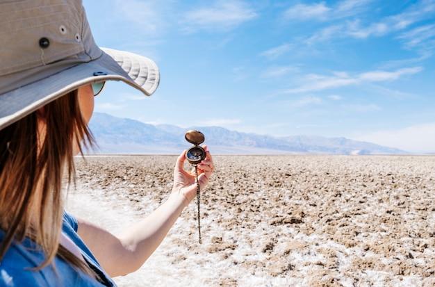 Una turista sosteniendo una brújula en medio del desierto del valle de la muerte en california, ee.uu., un día soleado durante su viaje