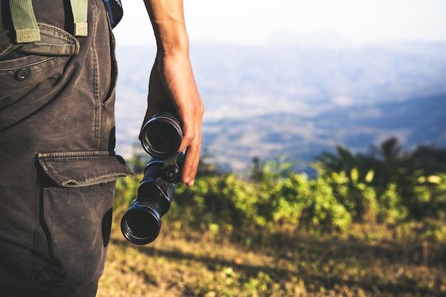 El turista se está sosteniendo a través de los prismáticos en el cielo nublado soleado de la tapa de la montaña.