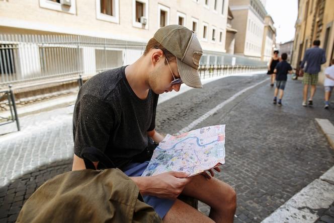 Turista teniendo en cuenta el mapa de la ciudad en roma