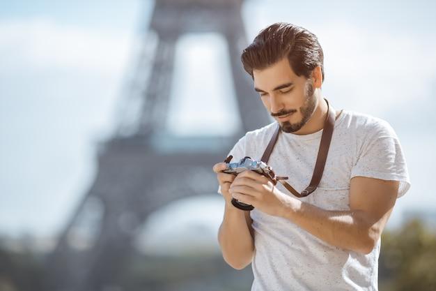 Turista de la torre eiffel con cámara tomando fotos frente a la torre eiffel, parís