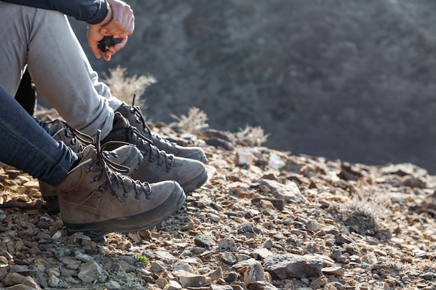 Turista en trekking botas de montaña caminando en la montaña al atardecer