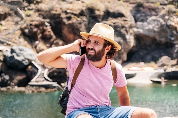 Un turista utiliza un teléfono móvil en una ciudad costera de el hierro, islas canarias