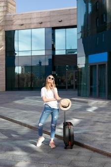 Turista en vasos con equipaje y sombrero en verano de vacaciones