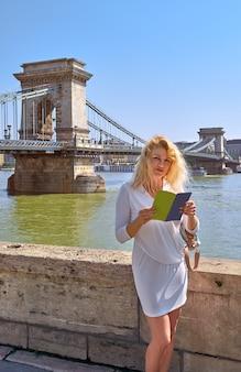 Turista en vestido blanco frente al famoso puente de las cadenas en budapest