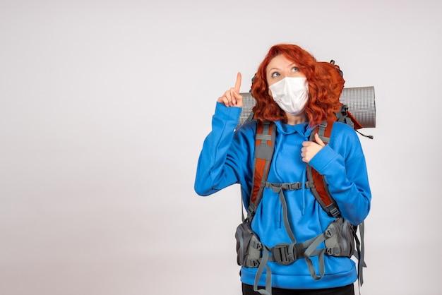 Turista de vista frontal en viaje de montaña en máscara con mochila