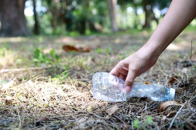 Turista voluntario mano limpiar basura y escombros de plástico en el bosque sucio gran bolsa azul
