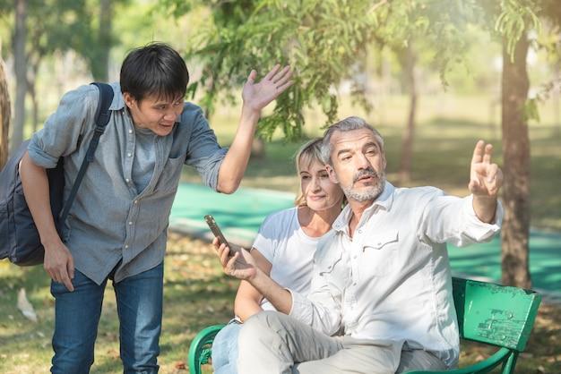 Turistas asiáticos joven con un teléfono móvil inteligente en sus manos pide instrucciones al anciano caucásico mayor que se sienta con una mujer, señaló con el dedo el camino.