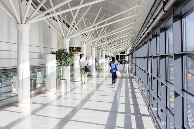 Los turistas están caminando por una puerta diferente siguiendo la etiqueta de la puerta con la flecha en la terminal del aeropuerto