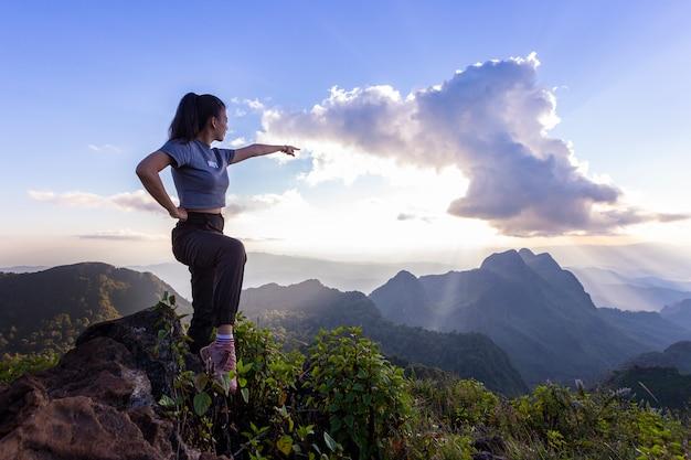 Los turistas están de pie en la cima de la montaña.