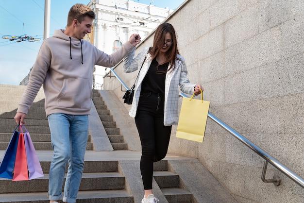 Los turistas felices caminan por la ciudad con compras y recuerdos en sus manos. guy ayuda a la niña a bajar las escaleras.