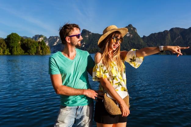 Turistas felices pasando tiempo juntos, novia mostrando algo interesante por su mano.