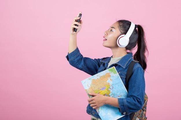 Turistas femeninos en el estudio en un fondo rosado.
