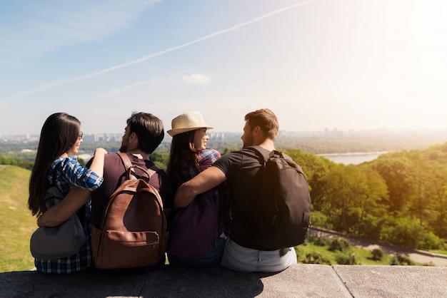 Los turistas jóvenes abrazan mirar hacia abajo en el paisaje escénico.