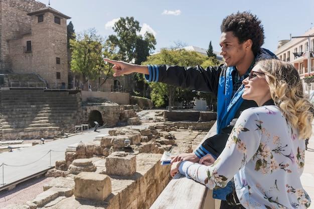 Turistas jóvenes en frente de un monumento