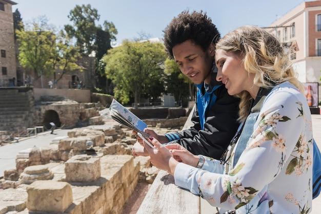 Turistas jóvenes mirando mapa en frente de monumento romano