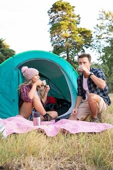 Turistas jóvenes sentados en la tienda y bebiendo té de termo. viajeros caucásicos acampando en la naturaleza y relajándose juntos en el césped. turismo de mochilero, aventura y concepto de vacaciones de verano.