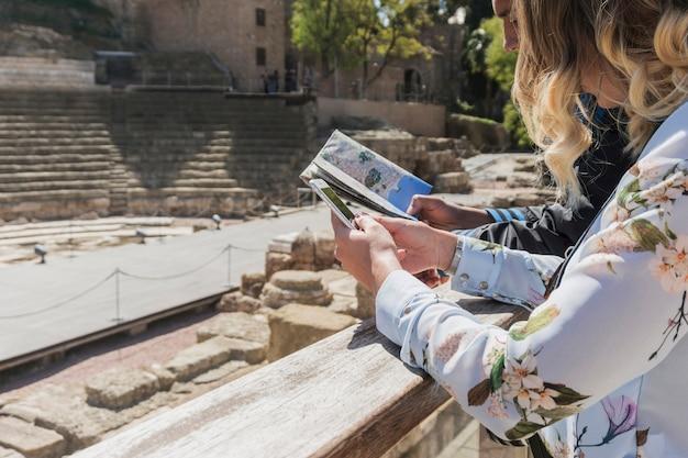 Turistas con mapa en frente de monumento romano