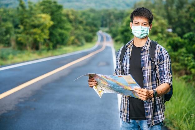Los turistas masculinos se paran y miran el mapa en el camino.