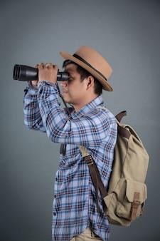 Turistas masculinos que hacen excursionismo sosteniendo el fondo del gris de los prismáticos.
