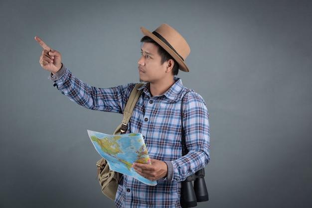 Turistas masculinos que llevan las mochilas que llevan un mapa gris del fondo.