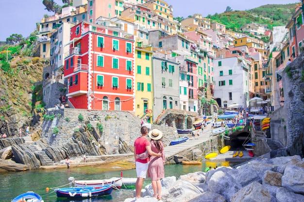 Turistas mirando la vista panorámica de riomaggiore, cinque terre, liguria, italia