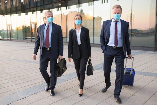 Turistas de negocios con máscaras faciales que visitan la oficina de socios extranjeros, maletas con ruedas, caminar al aire libre. vista frontal. viaje de negocios y concepto de epidemia.