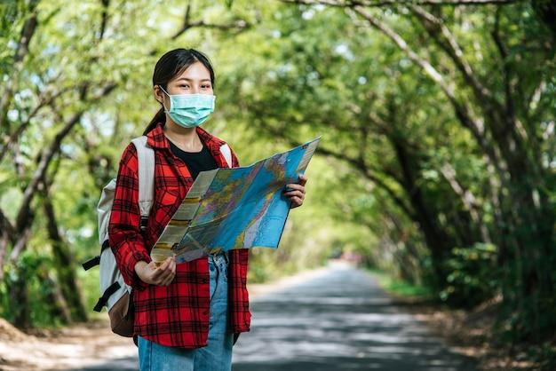 Las turistas se paran y miran el mapa en el camino.