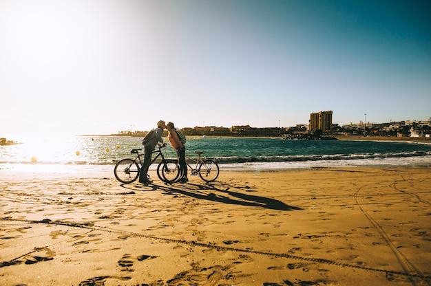 Turistas de pareja con bicicletas viendo puesta de sol.