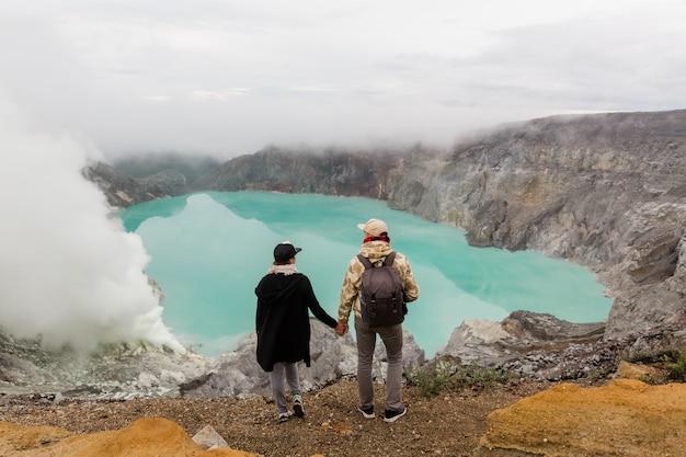 Los turistas de la pareja miran el lago del azufre en el volcán ijen en la isla java en indonesia. los excursionistas viajan en la cima de la montaña, concepto de viaje
