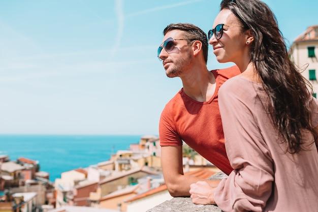 Turistas que miran la vista escénica de riomaggiore, cinque terre, liguria, italia