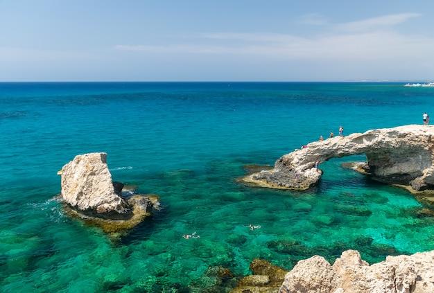 Los turistas saltan desde una altura a las aguas azules del mar mediterráneo.