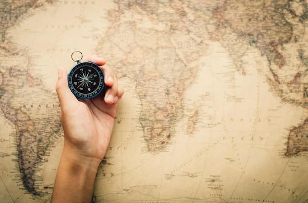 Los turistas sostienen una brújula y ubican un lugar en un mapa mundial.