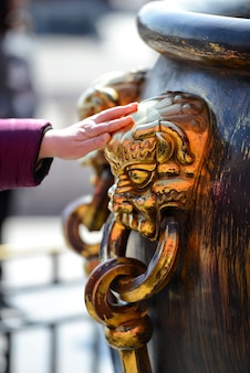 Los turistas tienen la suerte de tocar el mango de tazón grande con cabeza de león chino de bronce shinning en la ciudad prohibida en beijing, china