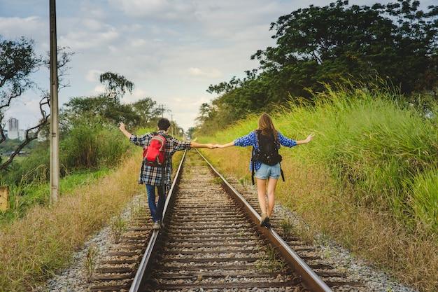 Turistas tomándose las manos en vías de tren