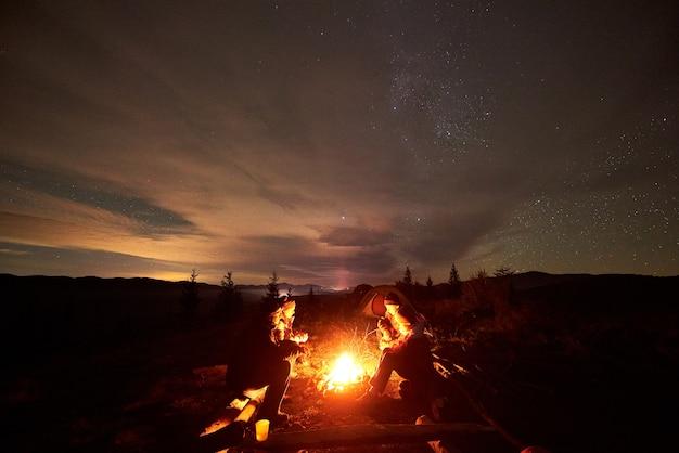 Turistas viajeros sentados junto a la quema de fogatas en el valle de la montaña bajo el cielo nublado estrellado.