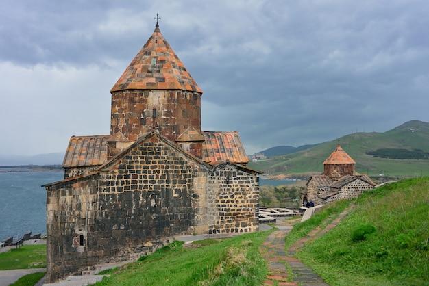 Los turistas visitan el monasterio sevanavank, ubicado en la península de sevan, entre las brillantes colinas verdes.