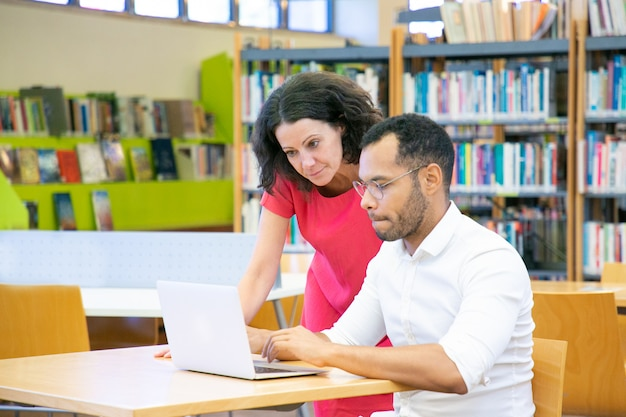 Tutor ayudando a estudiantes con investigación en biblioteca