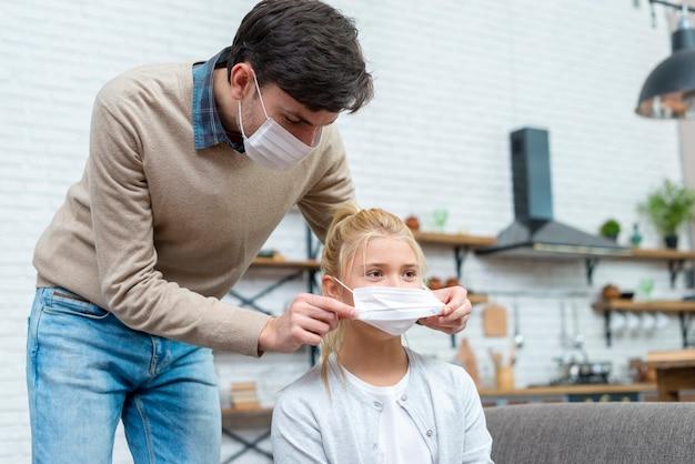 Tutor ayudando a la niña a ponerse la máscara