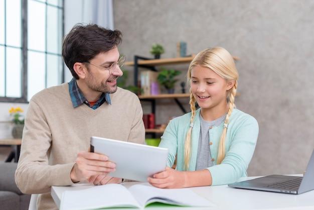 Tutor en casa y alumno usando una tableta digital