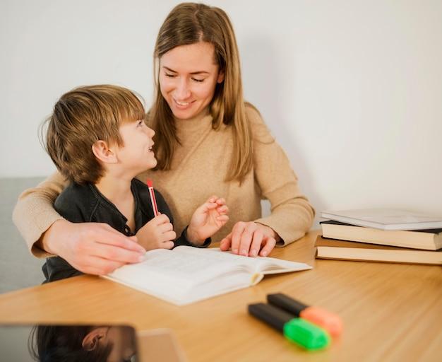Tutor femenino enseñando a niño en casa