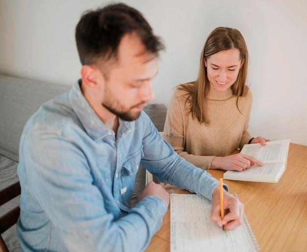 Tutor femenino que enseña al estudiante masculino en casa