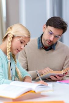 Tutor y niña en casa aprendiendo