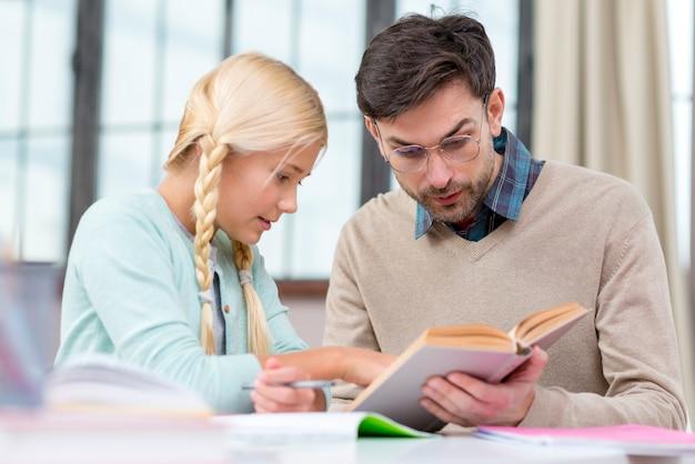 Tutor y niña en casa leyendo un libro