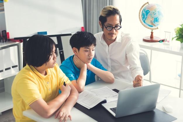 Tutor de niños en clase aprendiendo en computadora portátil