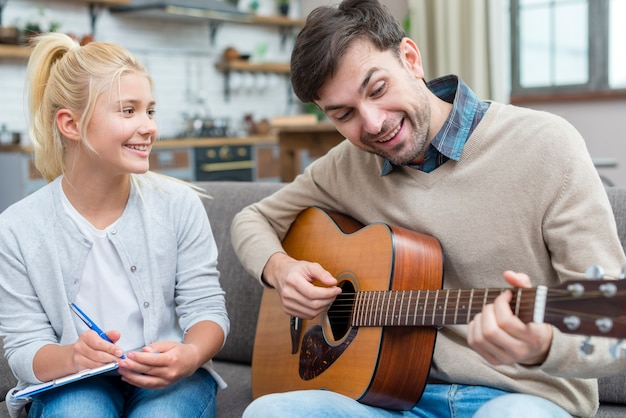 Tutor que muestra a su joven estudiante cómo tocar la guitarra