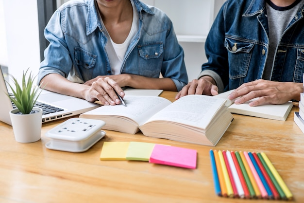 Tutor de secundaria o grupo de estudiantes universitarios sentados en el escritorio de la biblioteca estudiando y leyendo, haciendo la tarea y la práctica de la lección preparando el examen para el ingreso