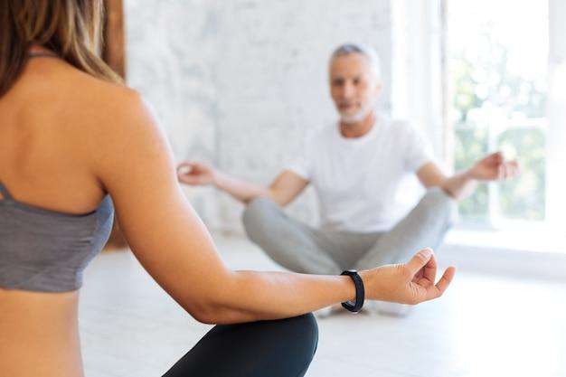 Tutor de yoga. varón frustrado cruzando las piernas y sentado en posición de yoga mientras medita